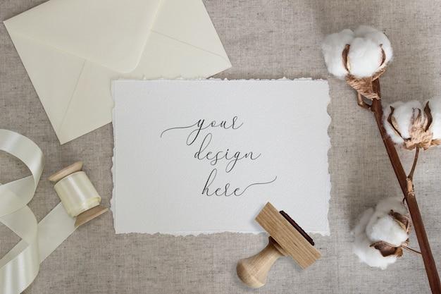 Gescheurde rand papieren kaart op linnen doek met katoenen bloemen en zijden lint. bruiloft briefpapier mockup. uitnodiging