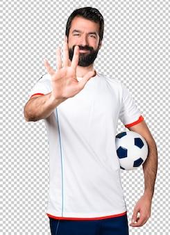 Giocatore di football americano che tiene un pallone da calcio che conta cinque