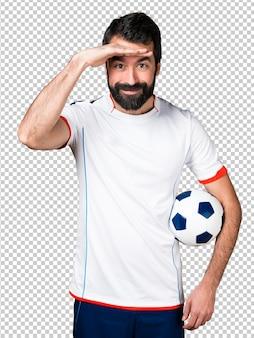 Giocatore di football americano che tiene un pallone da calcio che mostra qualcosa