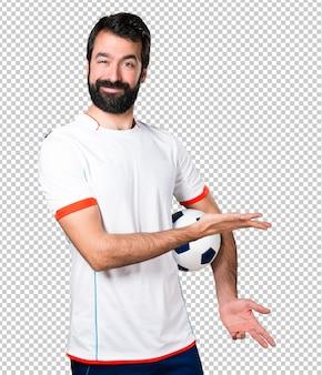 Giocatore di football americano che tiene un pallone da calcio che presenta qualcosa
