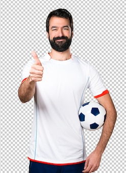 Giocatore di football americano che tiene un pallone da calcio con il pollice in su