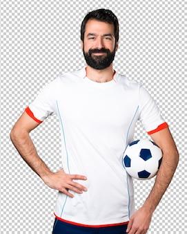 Giocatore di football americano felice che tiene un pallone da calcio
