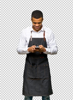 Giovane afro american barbiere inviando un messaggio con il cellulare