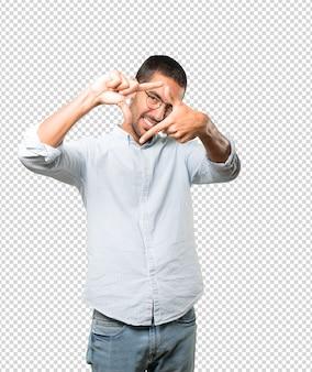 Giovane amichevole che fa un gesto di scattare una foto con le mani