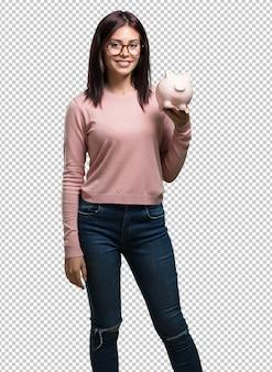 Giovane bella donna fiduciosa e allegra, con in mano una banca di maialini ed essendo silenziosa perché i soldi sono risparmiati, concetto di risparmio, economia e prosperità