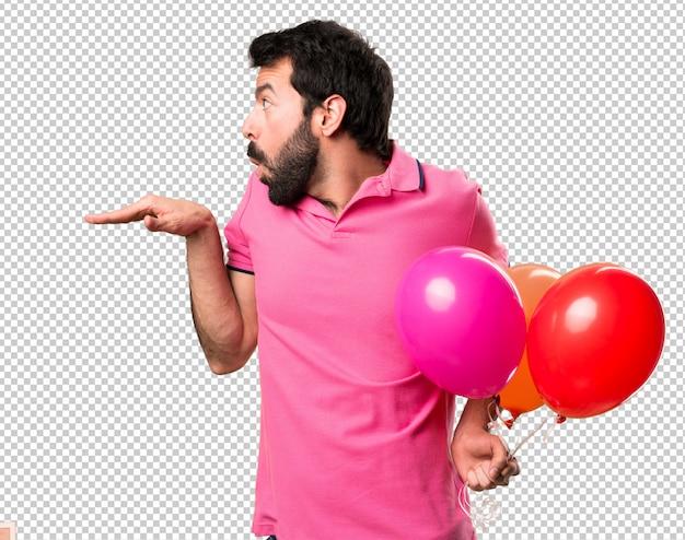 Giovane bello che tiene i palloni e ballare