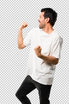Giovane con la camicia bianca che celebra una vittoria nella posizione del vincitore