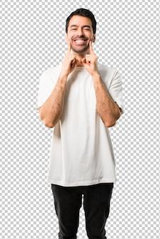 Giovane con la camicia bianca che sorride con un'espressione felice e piacevole