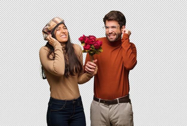 Giovane coppia in giorno di san valentino che copre le orecchie con le mani