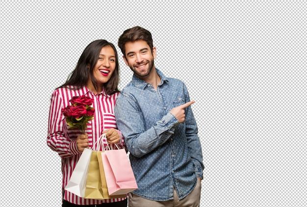 Giovane coppia in giorno di san valentino che punta verso il lato con il dito