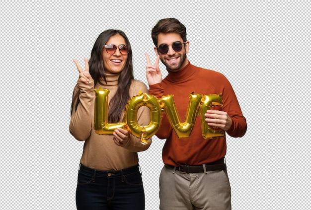 Giovane coppia in giorno di san valentino divertimento e felice facendo un gesto di vittoria