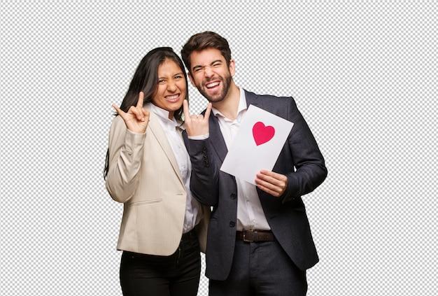 Giovane coppia in giorno di san valentino facendo un gesto di roccia