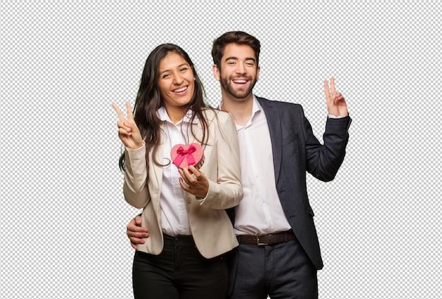 Giovane coppia in giorno di san valentino facendo un gesto di vittoria
