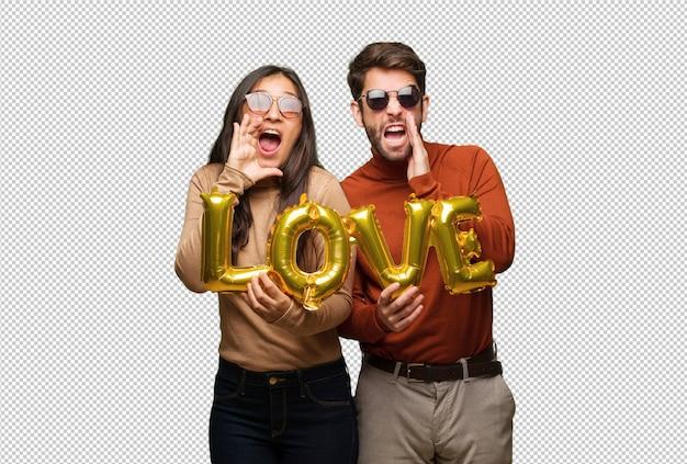 Giovane coppia in giorno di san valentino gridando qualcosa di felice per la parte anteriore