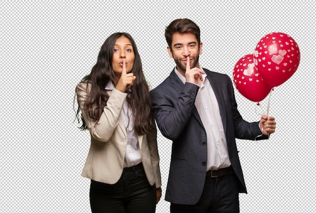 Giovane coppia in giorno di san valentino mantenendo un segreto o chiedendo il silenzio