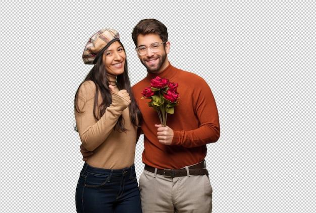 Giovane coppia in giorno di san valentino sorridendo e alzando il pollice in su