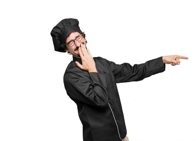 Giovane cuoco che ride forte qualcosa di esilarante e che punta di lato coprendo la bocca