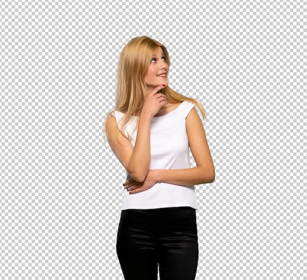 Giovane donna bionda che pensa un'idea mentre osserva in su