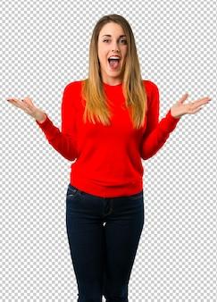 Giovane donna bionda con sorpresa e scioccata espressione facciale