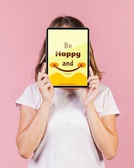 Giovane donna che copre il viso con un modello di tablet