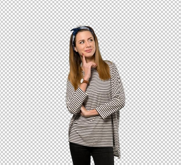 Giovane donna con il foulard che pensa un'idea mentre osserva in su