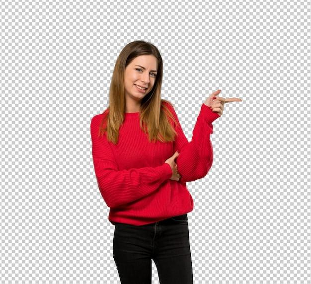 Giovane donna con maglione rosso che punta il dito verso il lato