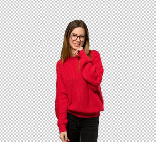 Giovane donna con maglione rosso con gli occhiali e sorridente