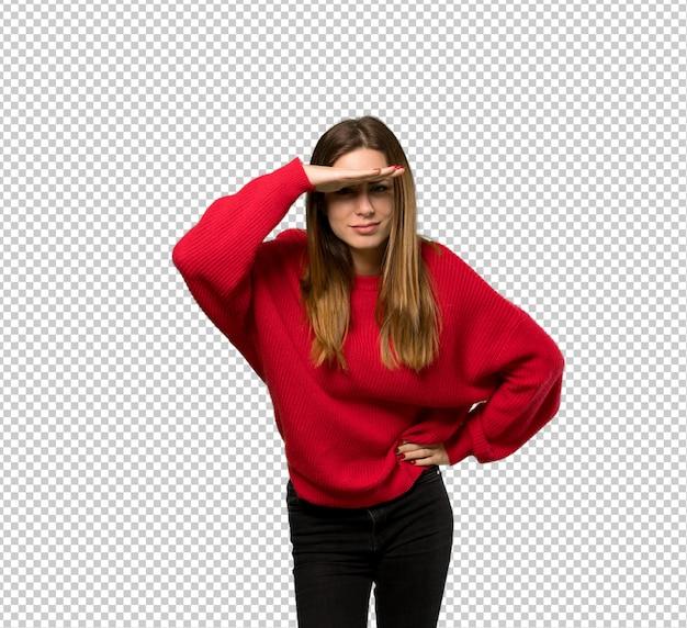 Giovane donna con maglione rosso guardando lontano con la mano per guardare qualcosa
