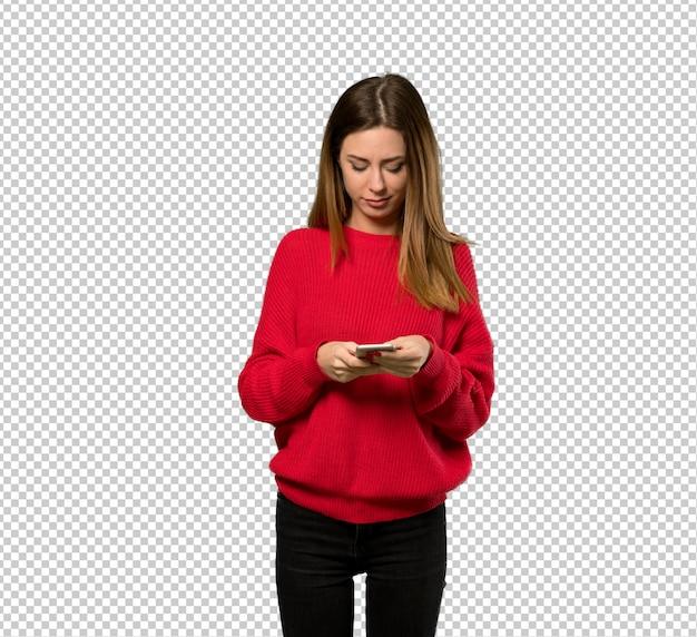 Giovane donna con maglione rosso inviando un messaggio con il cellulare