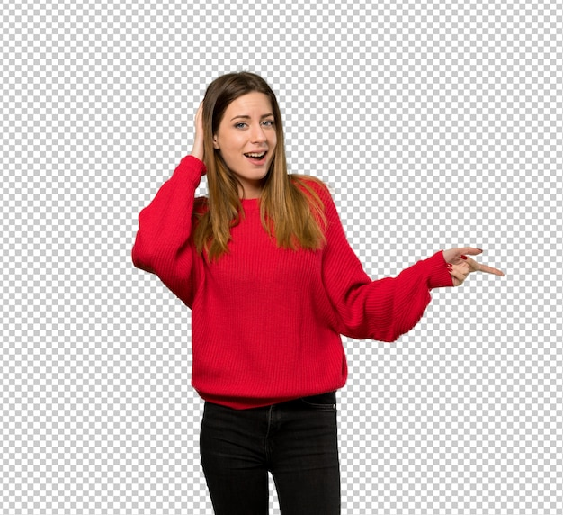 Giovane donna con maglione rosso sorpreso e puntando il dito sul lato