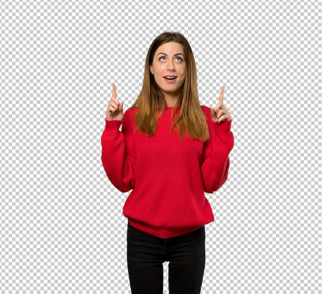 Giovane donna con maglione rosso sorpreso e rivolto verso l'alto