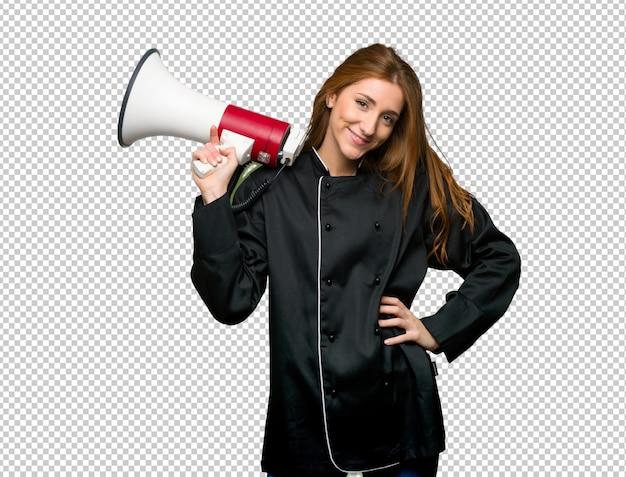Giovane donna del cuoco unico della testarossa che tiene un megafono