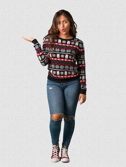 Giovane donna dell'ente completo che porta una tenuta della jersey di natale qualcosa sulla mano della palma