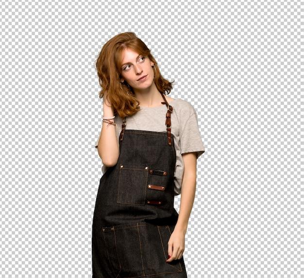 Giovane donna della testarossa con il grembiule che pensa un'idea mentre graffiando si dirige