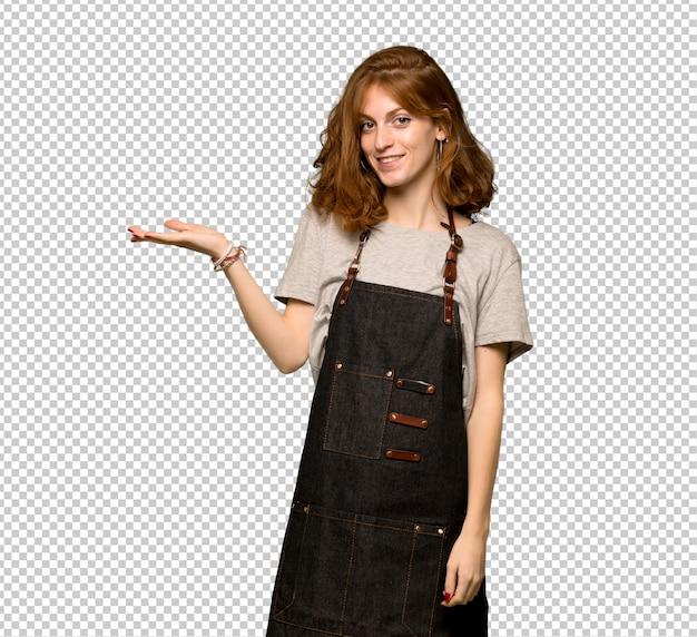 Giovane donna della testarossa con il grembiule che tiene immaginario del copyspace sulla palma per inserire un annuncio