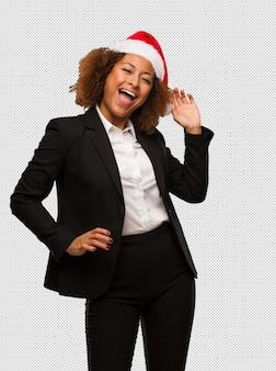 Giovane donna di affari nera che porta un cappello della santa di natale che balla e che si diverte