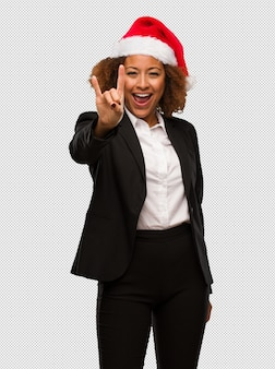Giovane donna di affari nera che porta un cappello della santa di natale che fa un gesto della roccia