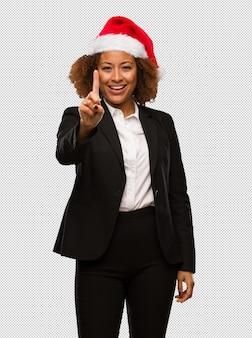 Giovane donna di affari nera che porta un cappello della santa di natale che mostra numero uno