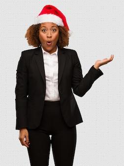 Giovane donna di affari nera che porta una tenuta del cappello di santa di natale qualcosa sulla mano della palma