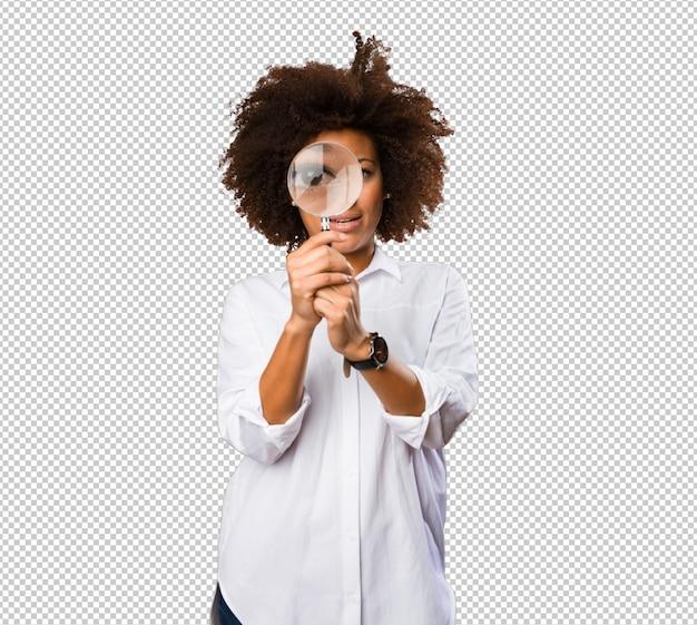 Giovane donna di colore che osserva tramite la lente d'ingrandimento