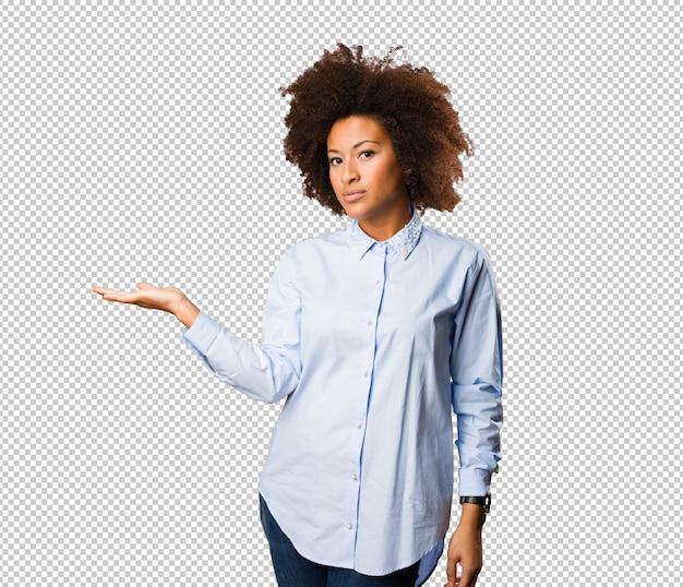 Giovane donna di colore che tiene qualcosa