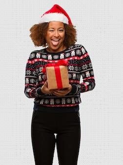 Giovane donna di colore che tiene un regalo nel giorno di natale funnny e lingua di mostra amichevole
