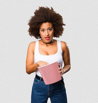 Giovane donna di colore che tiene un secchio del popcorn