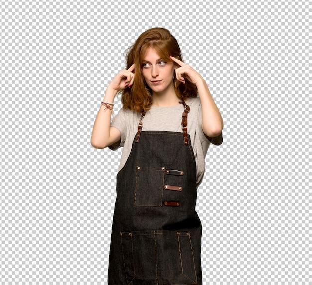 Giovane donna di redhead con il grembiule che ha dubbi e pensiero