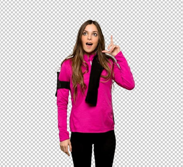 Giovane donna di sport che pensa un'idea che indica il dito su