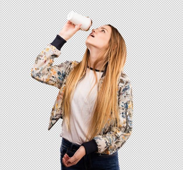 Giovane donna graziosa che mangia un caffè