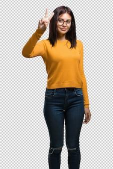 Giovane donna graziosa che mostra numero due, simbolo di conteggio, concetto di matematica