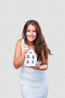Giovane donna graziosa che mostra un oggetto della casa
