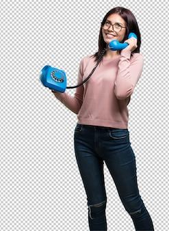 Giovane donna graziosa che ride ad alta voce mentre parla al telefono