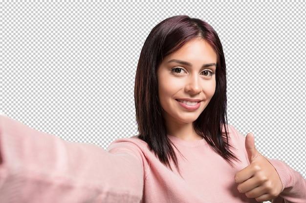 Giovane donna graziosa che sorride e felice, prendendo un selfie, tenendo la macchina fotografica, eccitata dalla sua vacanza o da un evento importante, espressione allegra
